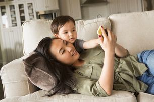 Woman lying on a sofa, smiling, cuddling with her young son and looking at a cell phone.の写真素材 [FYI02249305]