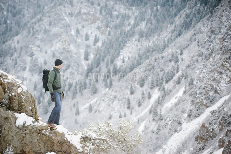 A man hiking in the mountains standing looking into a valley.の写真素材 [FYI02249318]