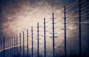 Power lines at regular intervals reaching into the distance against a patch of clearing sky and clouの写真素材 [FYI02249342]