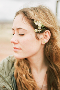 Head and shoulders portrait of a woman with a flower in her hair.の写真素材 [FYI02249363]