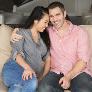 Smiling man and woman sitting on a sofa, hugging, and looking at the camera.の写真素材 [FYI02249365]