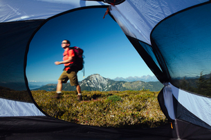 View from inside a camping tent of man hiking across national forest land with Mount Baker in the diの写真素材 [FYI02249375]