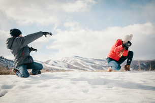 A snowball fight between a brother and sister.の写真素材 [FYI02249394]