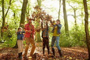 A family throwing dried leaves into the air in the woods in autumn.の写真素材 [FYI02249421]
