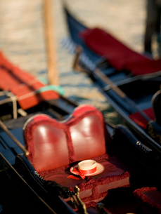 The red leather seat of a traditional gondola boat, and a straw boater with a ribbons around the croの写真素材 [FYI02249447]