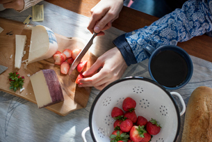 A woman slicing strawberries on a table with a wooden chopping board with a selection of cheeses andの写真素材 [FYI02249451]