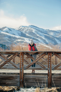 A girl in a red jacket with a woolly hat on leaning over the rail of a small footbridge.の写真素材 [FYI02249454]