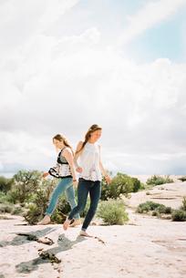 Two women running barefoot across the sand in a desert landscapeの写真素材 [FYI02249469]