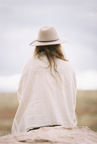 Rear view of a woman wearing a hat and wrap, sitting on a rock in a desert.の写真素材 [FYI02249481]
