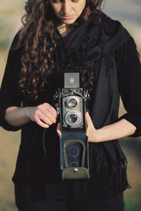 A woman taking a picture with an old fashioned medium format camera.の写真素材 [FYI02249485]