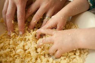 Two pairs of hands mixing ingredients in a bowl, an adult and a child cooking together.の写真素材 [FYI02249497]