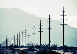 Power lines reaching into the distance, with a mountain backdrop.の写真素材 [FYI02249501]