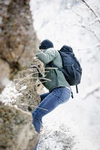 A man wearing a fleece jacket and hat, carrying a rucksack, climbing up a rocky cliff face.の写真素材 [FYI02249509]