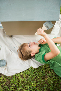 A boy in a garden, painting a dog house.の写真素材 [FYI02249511]