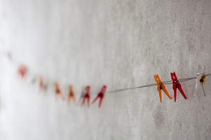 Coloured plastic clothes pegs on a washing line against a whitewashed wall.の写真素材 [FYI02249518]