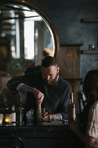 A woman and a bartender talking, and mixing drinks.の写真素材 [FYI02249522]