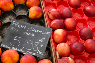 Boxes of nectarines on a fruit stall with a 有ice label.の写真素材 [FYI02249543]
