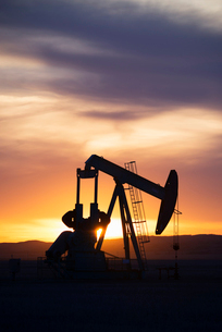 A pumpjack at an oil drilling site at sunset.の写真素材 [FYI02249544]