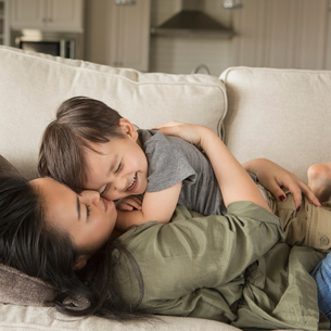 A woman lying on a sofa, smiling, cuddling her young son.の写真素材 [FYI02249546]