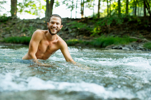 A young man swimming in a fast flowing cooling stream.の写真素材 [FYI02249566]