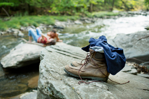 A young man and woman on the rocks on a river bank. Jeans and boots on a rock.の写真素材 [FYI02249602]