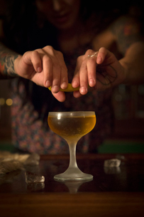A woman's hands squeezing a slice of lemon over a cocktail glass.の写真素材 [FYI02249614]