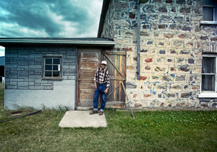 A farmer leaning against a doorjamb.の写真素材 [FYI02249623]