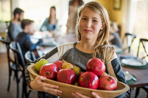 A girl carrying a basket of apples.の写真素材 [FYI02249635]