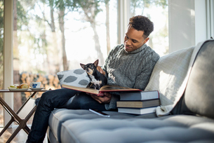 Man wearing a grey roll-neck jumper sitting on a sofa with a dog on his lap, looking at a book.の写真素材 [FYI02249677]