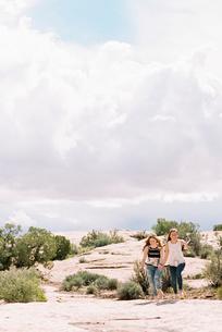 Two women running barefoot across the sand in a desert landscapeの写真素材 [FYI02249686]