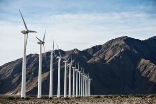 Wind power turbines in the landscape. A large number of turbine powers on a plain against a mountainの写真素材 [FYI02249692]