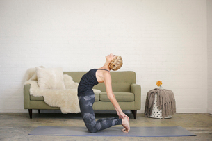 A blonde woman in a black leotard kneeling on a yoga mat, bending backwards with her hands touchingの写真素材 [FYI02249698]
