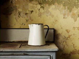 A vintage enamel jug of a traditional shape with a handle on an iron stove top.の写真素材 [FYI02249702]