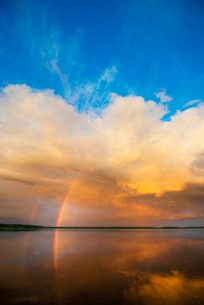 A rainbow and a dramatic cloud formation over a lake.の写真素材 [FYI02249722]
