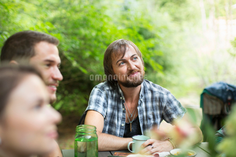 A group of three friends seated outdoors around a table, having a meal.の写真素材 [FYI02249742]