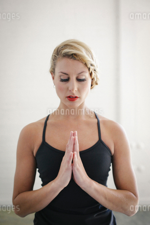 A blonde woman in a black leotard doing yoga, standing with her eyes closed and her hands together.の写真素材 [FYI02249746]