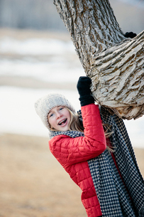 A young girl in a red jacket, and long scarf, gripping a tree trunk.の写真素材 [FYI02249752]