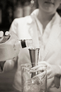 A woman mixing a cocktail, a mixologist at work.の写真素材 [FYI02249760]