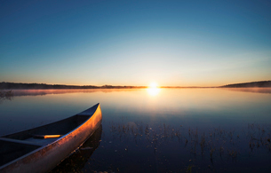 A canoe on a flat calm lake at sunset.の写真素材 [FYI02249763]