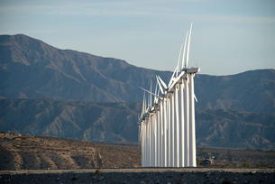 Wind power turbines in the landscape. A large number of turbine powers on a plain against a mountainの写真素材 [FYI02249768]
