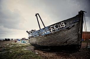 Abandoned wooden boat lying on a shingle beach.の写真素材 [FYI02249772]