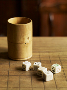 Five dice with printed faces, on a wooden pub table and a wooden cup beside them.の写真素材 [FYI02249775]