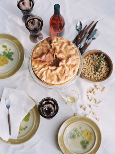 A table laid with dishes of food, nuts, cake, and a bottle of wine.の写真素材 [FYI02249781]
