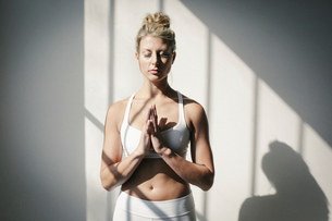 A blonde woman in a fitness clothes standing in front of a white wall with eyes closedの写真素材 [FYI02249787]