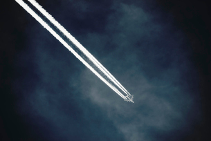 A jet with a clear condensation or vapour trail or contrail across a dark blue sky.の写真素材 [FYI02249794]