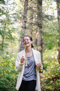 A woman standing in a glade in woodland holding two tall glasses of champagne.の写真素材 [FYI02249806]