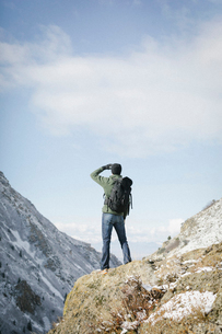 A man hiking in the mountains standing on an outcrop looking at the view.の写真素材 [FYI02249813]