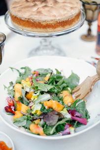 A fresh salad of young leaves, peach slices and a cake with meringue topping.の写真素材 [FYI02249821]