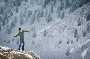 A man on a rock outcrop in the mountains.の写真素材 [FYI02249825]
