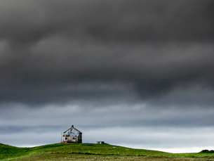 A barn on the crest of a hill, and dark storm clouds glowering over the land.の写真素材 [FYI02249836]